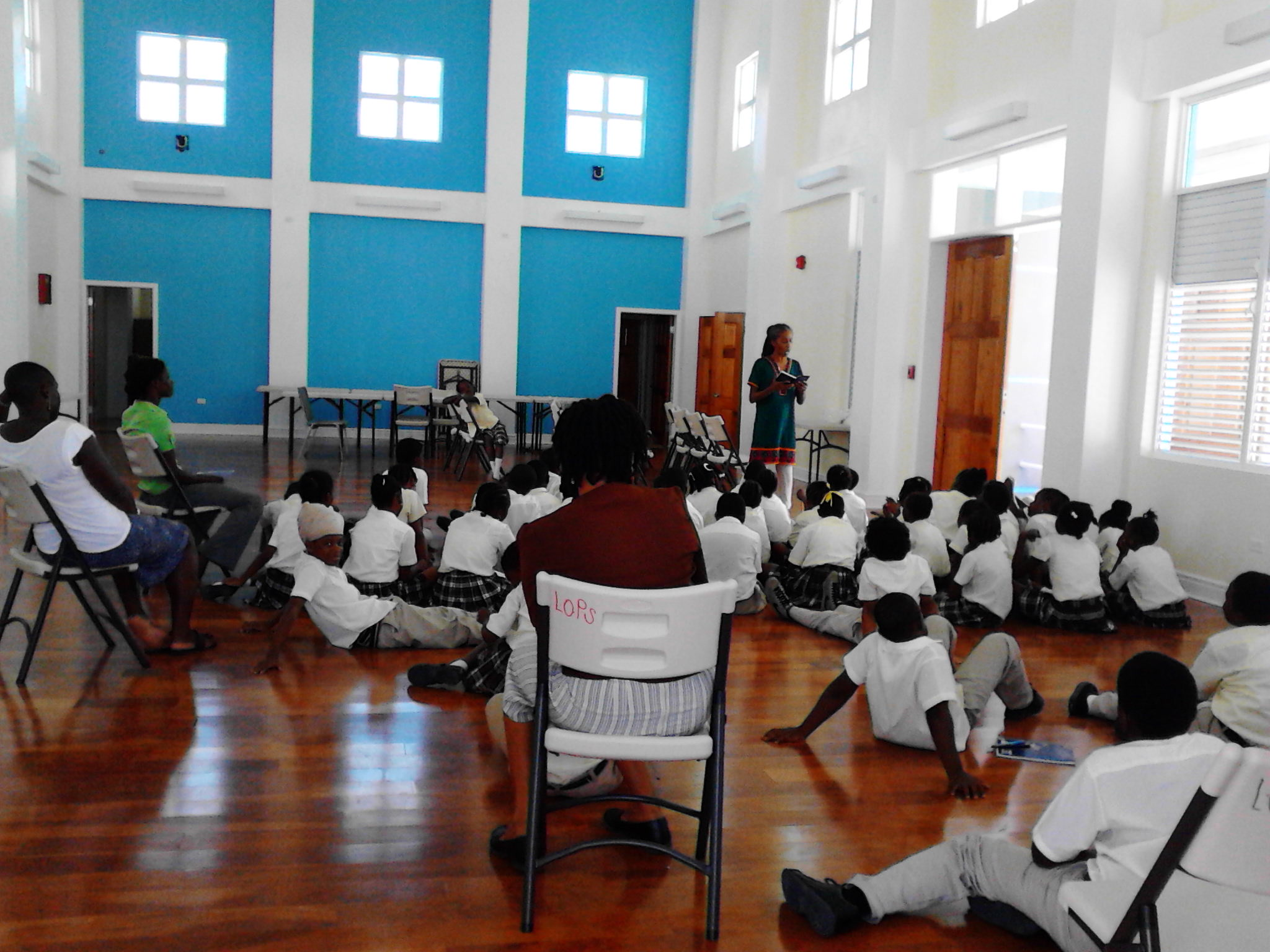 A-dZiko reads to children at Lookout Primary School